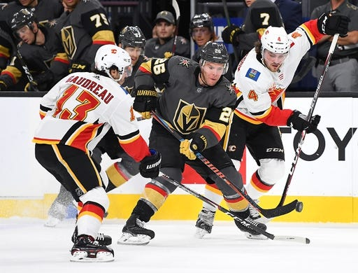Oct 12, 2019; Las Vegas, NV, USA; Vegas Golden Knights center Paul Stastny (26) flips the puck ahead of Calgary Flames left wing Johnny Gaudreau (13) and defenseman Rasmus Andersson (4) during the second period at T-Mobile Arena. Mandatory Credit: Stephen R. Sylvanie-USA TODAY Sports