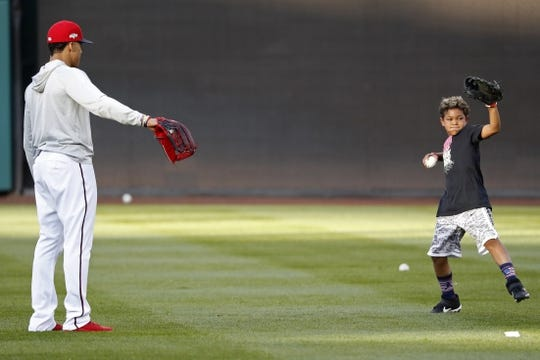 Oct 15, 2019; Washington, DC, USA; Washington Nationals left fielder Juan Soto (L) watches as Owen Kendrick (R), son of Nationals second baseman Howie Kendrick (not pictured) throws the ball during batting practice prior to the Nationals  game against the St. Louis Cardinals in game four of the 2019 NLCS playoff baseball series at Nationals Park. Mandatory Credit: Geoff Burke-USA TODAY Sports