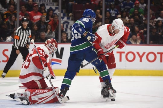 Oct 15, 2019; Vancouver, British Columbia, CAN; Vancouver Canucks forward Tim Schaller (59) battles for the puck against Detroit Red Wings defenseman Mike Green (25) and goaltender Jonathan Bernier (45) during the first period at Rogers Arena. Mandatory Credit: Anne-Marie Sorvin-USA TODAY Sports