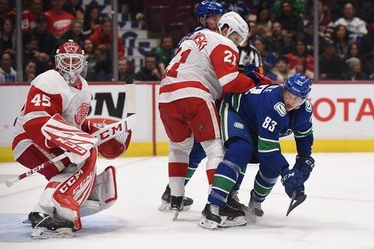 Oct 15, 2019; Vancouver, British Columbia, CAN; Detroit Red Wings defenseman Dennis Cholowski (21) and goaltender Jonathan Bernier (45) defend against Vancouver Canucks forward Jay Beagle (83) during the first period at Rogers Arena. Mandatory Credit: Anne-Marie Sorvin-USA TODAY Sports