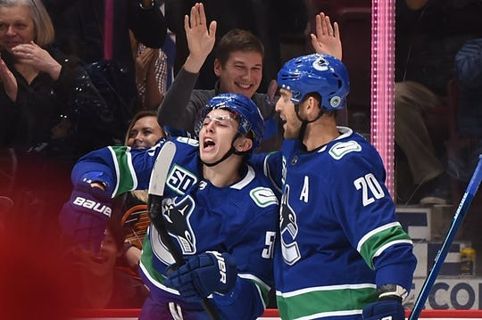 Oct 15, 2019; Vancouver, British Columbia, CAN; Vancouver Canucks defenseman Troy Stecher (51) celebrates his goal against Detroit Red Wings goaltender Jonathan Bernier (45) (not pictured) with forward Brandon Sutter (20) during the first period at Rogers Arena. Mandatory Credit: Anne-Marie Sorvin-USA TODAY Sports
