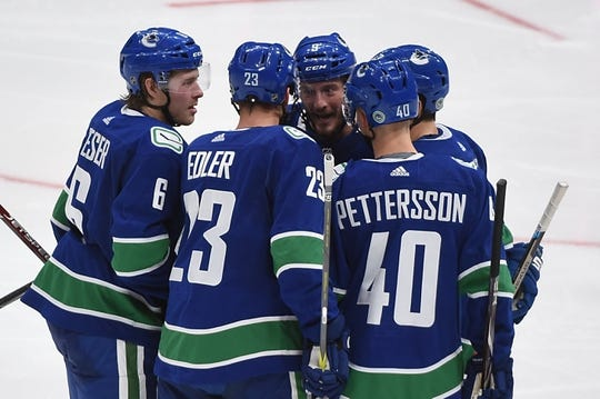 Oct 15, 2019; Vancouver, British Columbia, CAN; Vancouver Canucks defenseman Alexander Edler (23) celebrates his goal against Detroit Red Wings goaltender Jonathan Bernier (45) (not pictured) with Vancouver Canucks forward J.T. Miller (9) and forward Brock Boeser (6) and forward Elias Pettersson (40) during the second period at Rogers Arena. Mandatory Credit: Anne-Marie Sorvin-USA TODAY Sports