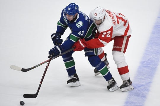 Oct 15, 2019; Vancouver, British Columbia, CAN; Detroit Red Wings forward Andreas Athanasiou (72) reaches across Vancouver Canucks defenseman Quinn Hughes (43) for the puck during the second period at Rogers Arena. Mandatory Credit: Anne-Marie Sorvin-USA TODAY Sports