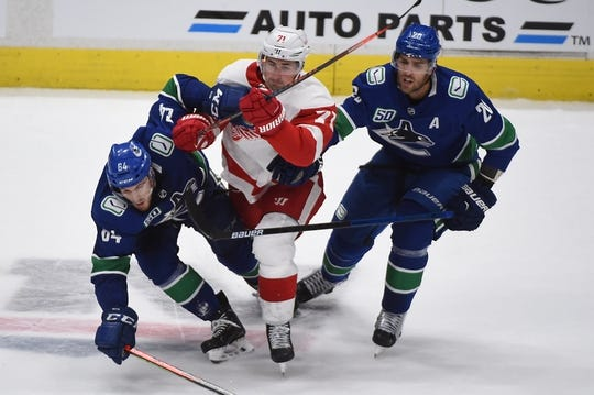 Oct 15, 2019; Vancouver, British Columbia, CAN; Vancouver Canucks forward Tyler Motte (64) and forward Brandon Sutter (20) defend against Detroit Red Wings forward Dylan Larkin (71) during the second period at Rogers Arena. Mandatory Credit: Anne-Marie Sorvin-USA TODAY Sports