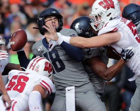 Oct 19, 2019; Champaign, IL, USA; Illinois Fighting Illini quarterback Brandon Peters (18) is sacked by Wisconsin Badgers linebacker Zack Baun (56) during the first quarter at Memorial Stadium. Mandatory Credit: Mark Hoffman/Milwaukee Journal Sentinel via USA TODAY Sports