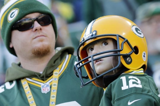 Oct 20, 2019; Green Bay, WI, USA; Green Bay Packers fans Mike Meredith (left) and his son Mason (right) of Norfolk, VA, watch players warm up prior to the game against the Oakland Raiders at Lambeau Field. Mandatory Credit: Dan Powers/Wisconsin via USA TODAY Sports