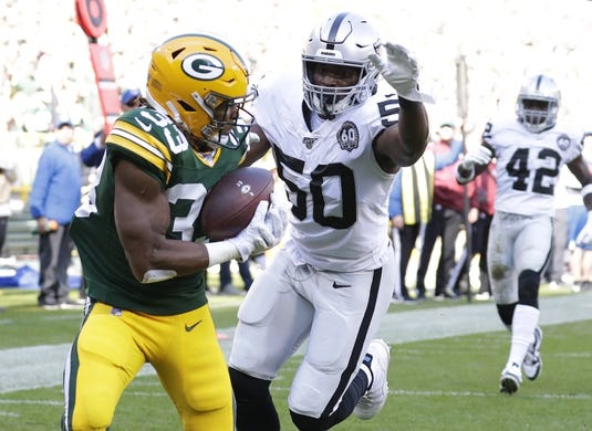 Oct 20, 2019; Green Bay, WI, USA; Green Bay Packers running back Aaron Jones (33) scores a touchdown reception in front of Oakland Raiders linebacker Nicholas Morrow (50) in the first quarter at Lambeau Field. Mandatory Credit: Dan Powers/Wisconsin via USA TODAY Sports