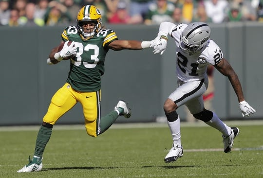 Oct 20, 2019; Green Bay, WI, USA; Green Bay Packers running back Aaron Jones (33) carries the ball past Oakland Raiders cornerback Gareon Conley (21) in the first quarter at Lambeau Field. Mandatory Credit: Dan Powers/Wisconsin via USA TODAY Sports