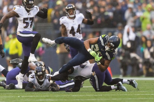Oct 20, 2019; Seattle, WA, USA; Seattle Seahawks running back C.J. Prosise (22) dives over Baltimore Ravens cornerback Brandon Carr (39) during the first half at CenturyLink Field. Mandatory Credit: Steven Bisig-USA TODAY Sports