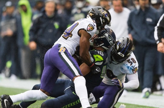 Oct 20, 2019; Seattle, WA, USA; Baltimore Ravens cornerback Marlon Humphrey (44) and Baltimore Ravens linebacker L.J. Fort (58) tackle Seattle Seahawks tight end Jacob Hollister (48) during the first half at CenturyLink Field. Baltimore defeated Seattle 30-16. Mandatory Credit: Steven Bisig-USA TODAY Sports