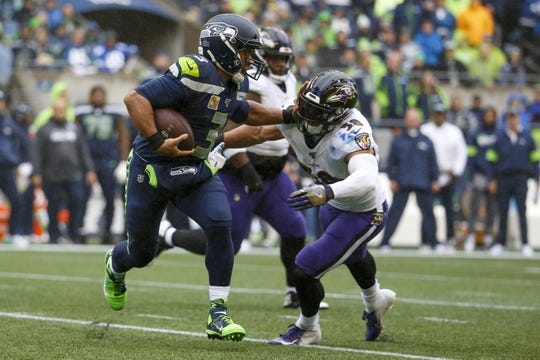 Oct 20, 2019; Seattle, WA, USA; Seattle Seahawks quarterback Russell Wilson (3) stiff arms away from Baltimore Ravens linebacker L.J. Fort (58) during the first quarter at CenturyLink Field. Mandatory Credit: Joe Nicholson-USA TODAY Sports