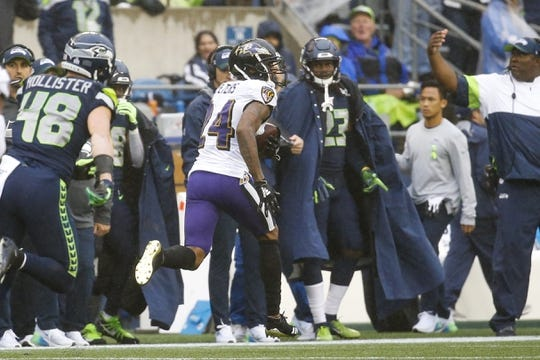 Oct 20, 2019; Seattle, WA, USA; Baltimore Ravens cornerback Marcus Peters (24) returns an interception for a touchdown during the second quarter against the Seattle Seahawks at CenturyLink Field. Mandatory Credit: Joe Nicholson-USA TODAY Sports