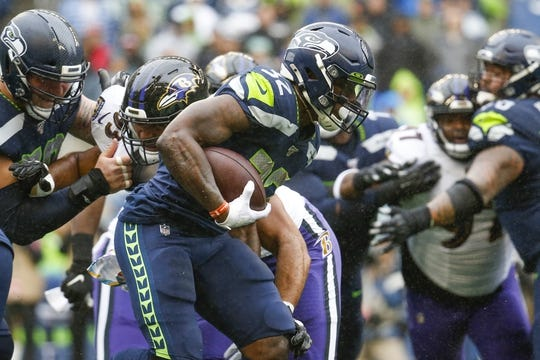 Oct 20, 2019; Seattle, WA, USA; Seattle Seahawks running back Chris Carson (32) breaks a tackle by Baltimore Ravens nose tackle Chris Wormley (93) during the first quarter at CenturyLink Field. Mandatory Credit: Joe Nicholson-USA TODAY Sports