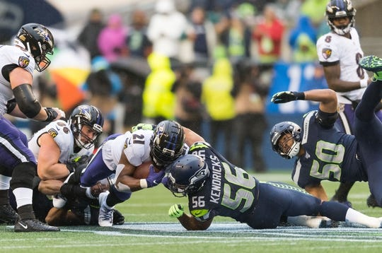 Oct 20, 2019; Seattle, WA, USA; Baltimore Ravens running back Mark Ingram (21) dives for extra yards while being tackled by Seattle Seahawks linebacker Mychal Kendricks (56) during the second half at CenturyLink Field. Baltimore defeated Seattle 30-16. Mandatory Credit: Steven Bisig-USA TODAY Sports