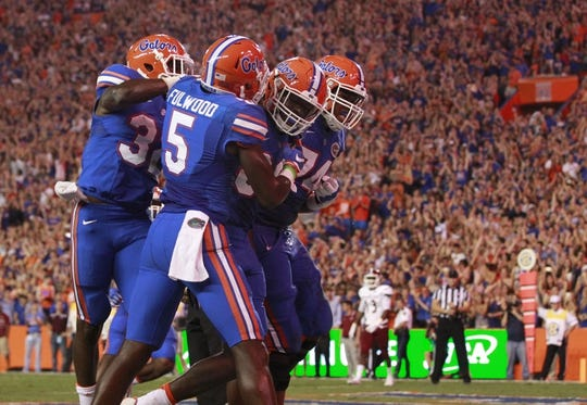 Sep 5, 2015; Gainesville, FL, USA;  Florida Gators tight end C'yontai Lewis (80) is congratulated by wide receiver Brandon Powell (4) and teammates as he scores a touchdown against the New Mexico State Aggies during the second quarter at Ben Hill Griffin Stadium. Mandatory Credit: Kim Klement-USA TODAY Sports