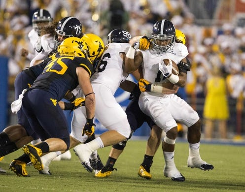 Sep 5, 2015; Morgantown, WV, USA; Georgia Southern Eagles running back LA Ramsby is stopped in the backfield by West Virginia Mountaineers defenders during the second quarter at Milan Puskar Stadium. Mandatory Credit: Ben Queen-USA TODAY Sports