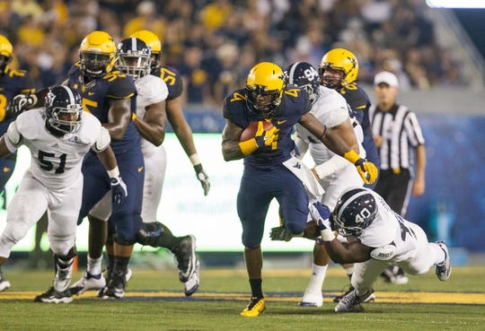 Sep 5, 2015; Morgantown, WV, USA; West Virginia Mountaineers running back Wendell Smallwood breaks a tackle during the second quarter against the Georgia Southern Eagles at Milan Puskar Stadium. Mandatory Credit: Ben Queen-USA TODAY Sports