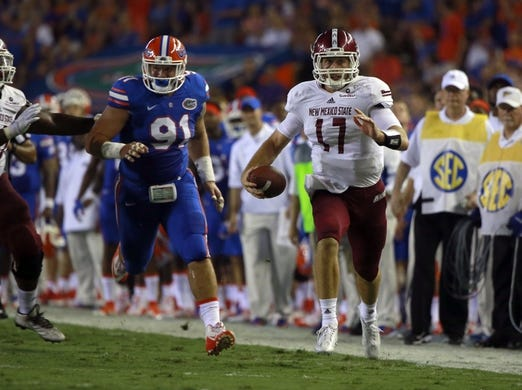 Sep 5, 2015; Gainesville, FL, USA; New Mexico State Aggies quarterback Tyler Rogers (17) runs with the ball against the Florida Gators during the second quarter at Ben Hill Griffin Stadium. Mandatory Credit: Kim Klement-USA TODAY Sports