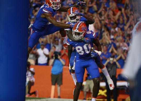 Sep 5, 2015; Gainesville, FL, USA; Florida Gators tight end C'yontai Lewis (80) is congratulated by wide receiver Brandon Powell (4) and teammates  as he ran the ball in for a touchdown against the New Mexico State Aggies during the second quarter at Ben Hill Griffin Stadium. Mandatory Credit: Kim Klement-USA TODAY Sports