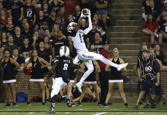 Sep 5, 2015; Cincinnati, OH, USA; Alabama A&M Bulldogs wide receiver DeVon Johnson (13) makes a catch while being defended by Cincinnati Bearcats cornerback Adrian Witty (8) in the first half at Nippert Stadium. Mandatory Credit: Aaron Doster-USA TODAY Sports