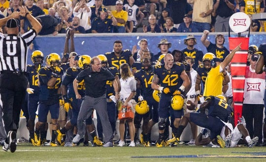 Sep 5, 2015; Morgantown, WV, USA; The West Virginia Mountaineers bench celebrates as safety Karl Joseph makes an interception on the third quarter against the Georgia Southern Eagles at Milan Puskar Stadium. Mandatory Credit: Ben Queen-USA TODAY Sports
