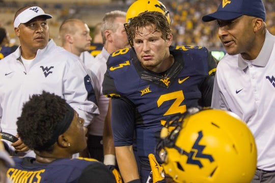Sep 5, 2015; Morgantown, WV, USA; West Virginia Mountaineers quarterback Skyler Howard talks with coaches and players on the sidelines after a score during the third quarter against the Georgia Southern Eagles at Milan Puskar Stadium.  Mandatory Credit: Ben Queen-USA TODAY Sports