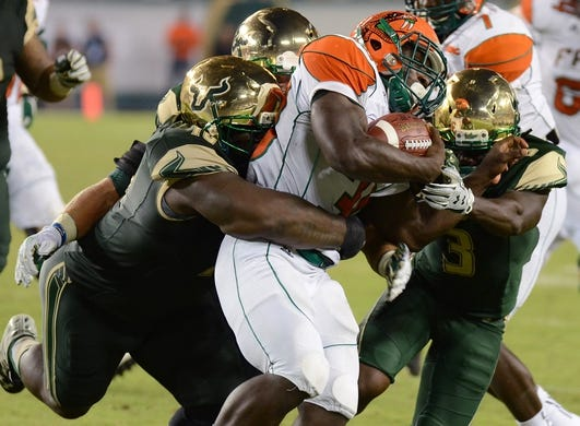 Sep 5, 2015; Tampa, FL, USA; Florida A & M Rattlers  running back Gerald Hearns (30) gets tackled by a group of  South Florida Bulls in the second half  at Raymond James Stadium. Mandatory Credit: Jonathan Dyer-USA TODAY Sports