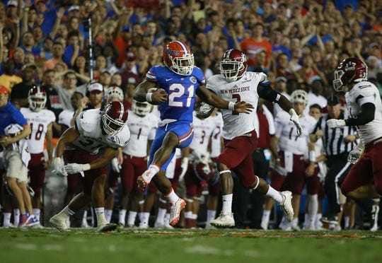 Sep 5, 2015; Gainesville, FL, USA Florida Gators running back Kelvin Taylor (21) runs past  New Mexico State Aggies linebacker Terrill Hanks (2) and safety Jaden Wright (21)  during the first quarter at Ben Hill Griffin Stadium. Mandatory Credit: Kim Klement-USA TODAY Sports