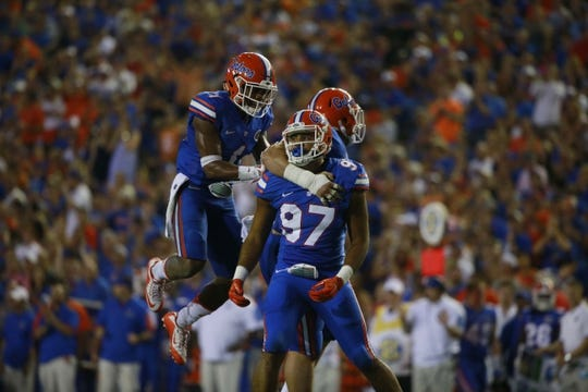 Sep 5, 2015; Gainesville, FL, USA; Florida Gators defensive lineman Justus Reed (97) is congratulated by defensive back Vernon Hargreaves III (1) and teammates as he sacks New Mexico State Aggies quarterback Tyler Rogers (17) (not pictured) during the second half at Ben Hill Griffin Stadium. Mandatory Credit: Kim Klement-USA TODAY Sports