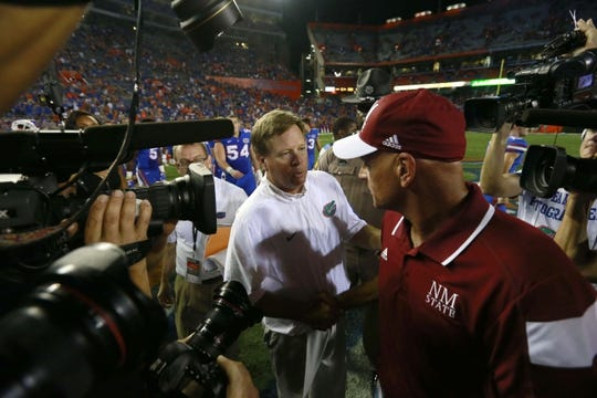 Sep 5, 2015; Gainesville, FL, USA; Florida Gators head coach Jim McElwain and New Mexico State Aggies head coach Doug Martin meet after the game at Ben Hill Griffin Stadium. Florida Gators defeated the New Mexico State Aggies 61-13. Mandatory Credit: Kim Klement-USA TODAY Sports