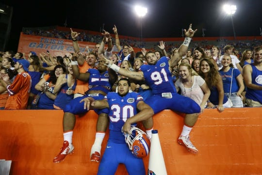 Sep 5, 2015; Gainesville, FL, USA; Florida Gators defensive lineman Joey Ivie (91), Florida Gators offensive lineman Andrew Mike (77) and teammates celebrate as they beat the New Mexico State Aggies at Ben Hill Griffin Stadium. Florida Gators defeated the New Mexico State Aggies 61-13. Mandatory Credit: Kim Klement-USA TODAY Sports