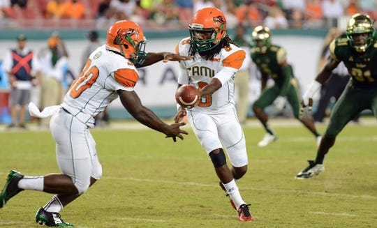 Sep 5, 2015; Tampa, FL, USA; Florida A & M Rattlers  quarterback Kenneth Coleman (8) hands the ball off in the second half against South Florida Bulls  the  at Raymond James Stadium. Mandatory Credit: Jonathan Dyer-USA TODAY Sports