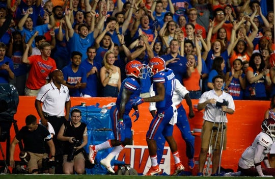 Sep 5, 2015; Gainesville, FL, USA Florida Gators wide receiver Brandon Powell (4) is congratulated by Florida Gators wide receiver Demarcus Robinson (11) and teammates as he scored a touchdown against the New Mexico State Aggies during the first quarter at Ben Hill Griffin Stadium. Mandatory Credit: Kim Klement-USA TODAY Sports