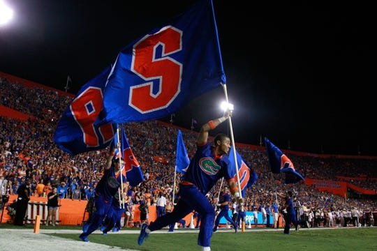 Sep 5, 2015; Gainesville, FL, USA; Florida Gators cheerleaders run flags on the field after they scored a touchdown against the New Mexico State Aggies during the second half at Ben Hill Griffin Stadium. Florida Gators defeated the New Mexico State Aggies 61-13. Mandatory Credit: Kim Klement-USA TODAY Sports