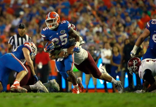 Sep 5, 2015; Gainesville, FL, USA; Florida Gators running back Jordan Scarlett (25) runs as New Mexico State Aggies defensive lineman Stephen Meredith (99) defends during the second half at Ben Hill Griffin Stadium. Mandatory Credit: Kim Klement-USA TODAY Sports