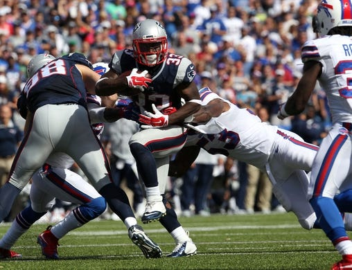 Sep 20, 2015; Orchard Park, NY, USA; New England Patriots running back Dion Lewis (33) runs the ball and avoids a tackle by Buffalo Bills outside linebacker Nigel Bradham (53) at Ralph Wilson Stadium. Patriots defeat the Bills 40 to 32.  Mandatory Credit: Timothy T. Ludwig-USA TODAY Sports