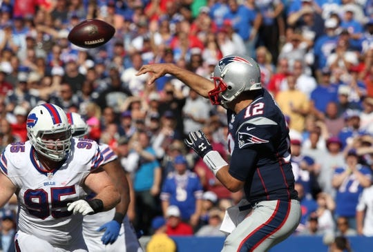 Sep 20, 2015; Orchard Park, NY, USA; New England Patriots quarterback Tom Brady (12) throws a pass while avoiding a tackle by Buffalo Bills defensive tackle Kyle Williams (95) during the second half at Ralph Wilson Stadium. Patriots defeat the Bills 40 to 32.  Mandatory Credit: Timothy T. Ludwig-USA TODAY Sports