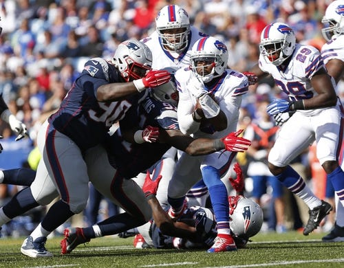 Sep 20, 2015; Orchard Park, NY, USA; Buffalo Bills quarterback Tyrod Taylor (5) is sacked by New England Patriots outside linebacker Jamie Collins (91) and defensive tackle Malcom Brown (90) during the second half at Ralph Wilson Stadium. Patriots beat the Bills 40-32. Mandatory Credit: Kevin Hoffman-USA TODAY Sports