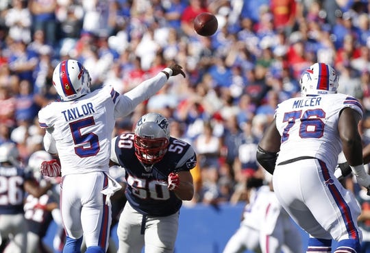 Sep 20, 2015; Orchard Park, NY, USA; Buffalo Bills quarterback Tyrod Taylor (5) throws a pass as he is hit by New England Patriots defensive end Rob Ninkovich (50) during the second half at Ralph Wilson Stadium. Patriots beat the Bills 40-32. Mandatory Credit: Kevin Hoffman-USA TODAY Sports