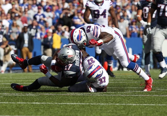 Sep 20, 2015; Orchard Park, NY, USA; New England Patriots wide receiver Aaron Dobson (17) gets tackled by Buffalo Bills defensive back Nickell Robey (37) and Buffalo Bills outside linebacker Nigel Bradham (53) during the second half at Ralph Wilson Stadium. Patriots defeat the Bills 40 to 32.  Mandatory Credit: Timothy T. Ludwig-USA TODAY Sports