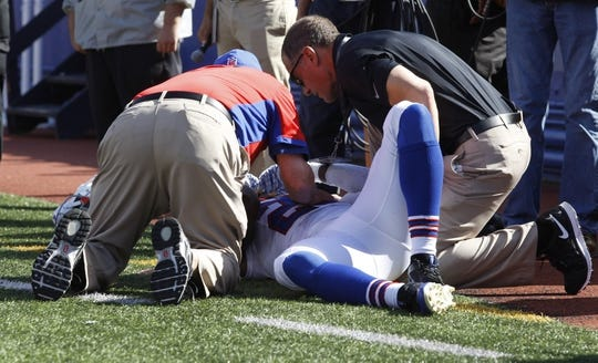 Sep 20, 2015; Orchard Park, NY, USA; Buffalo Bills strong safety Aaron Williams (23) is attended to by trainers after getting hurt during the second half against the New England Patriots at Ralph Wilson Stadium. Patriots defeat the Bills 40 to 32.  Mandatory Credit: Timothy T. Ludwig-USA TODAY Sports