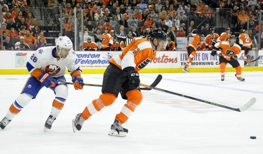 Sep 21, 2015; Philadelphia, PA, USA; Philadelphia Flyers defenseman Yevgeni Medvedev (82) skates past New York Islanders center Bracken Kearns (28) during the first period at PPL Center. Mandatory Credit: Eric Hartline-USA TODAY Sports