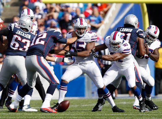 Sep 20, 2015; Orchard Park, NY, USA; Buffalo Bills defensive end Jerry Hughes (55) strips the ball from New England Patriots quarterback Tom Brady (12) during the second half at Ralph Wilson Stadium. Mandatory Credit: Kevin Hoffman-USA TODAY Sports