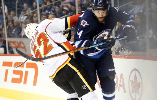 Oct 1, 2015; Winnipeg, Manitoba, CAN; Winnipeg Jets  forward  Anthony Peluso (14) collides with Calgary Flames left wing Brandon Bollig (52) during the first period at MTS Centre. Mandatory Credit: Bruce Fedyck-USA TODAY Sports