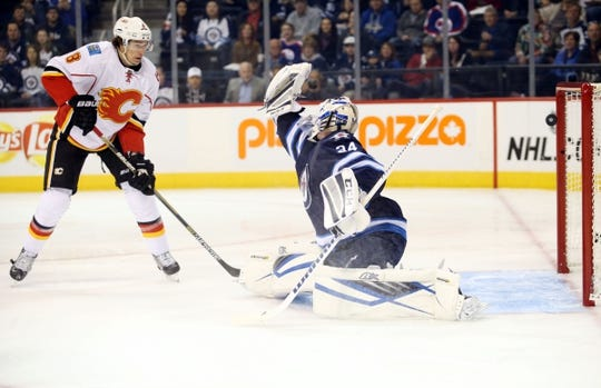 Oct 1, 2015; Winnipeg, Manitoba, CAN; Calgary Flames defenseman Deryk Engelland (not shown) shoots the puck past Winnipeg Jets  goalie Michael Hutchinson (34) during the first period at MTS Centre. Mandatory Credit: Bruce Fedyck-USA TODAY Sports