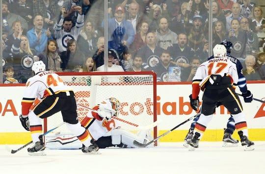 Oct 1, 2015; Winnipeg, Manitoba, CAN; Winnipeg Jets  forward  Mark Scheifele (55) celebrates his goal on Calgary Flames goalie Joni Ortio (37) during the first period at MTS Centre. Mandatory Credit: Bruce Fedyck-USA TODAY Sports