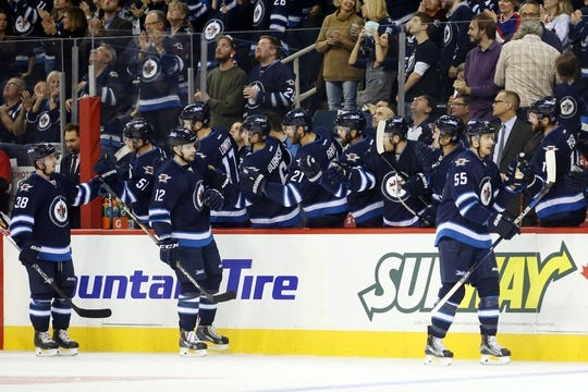 Oct 1, 2015; Winnipeg, Manitoba, CAN; Winnipeg Jets  forward  Mark Scheifele (55) celebrates his goal with teammates against the Calgary Flames during the first period at MTS Centre. Mandatory Credit: Bruce Fedyck-USA TODAY Sports