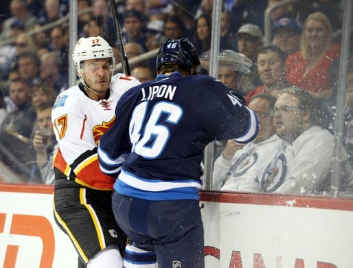Oct 1, 2015; Winnipeg, Manitoba, CAN; Winnipeg Jets  forward  J.C. Lipon (46) collides with Calgary Flames left wing Lance Bouma (17) during the first period at MTS Centre. Mandatory Credit: Bruce Fedyck-USA TODAY Sports