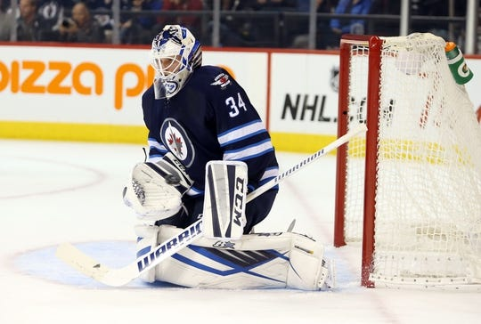 Oct 1, 2015; Winnipeg, Manitoba, CAN; Winnipeg Jets  goalie  Michael Hutchinson (34) makes a save during the first period against the Calgary Flames at MTS Centre. Mandatory Credit: Bruce Fedyck-USA TODAY Sports