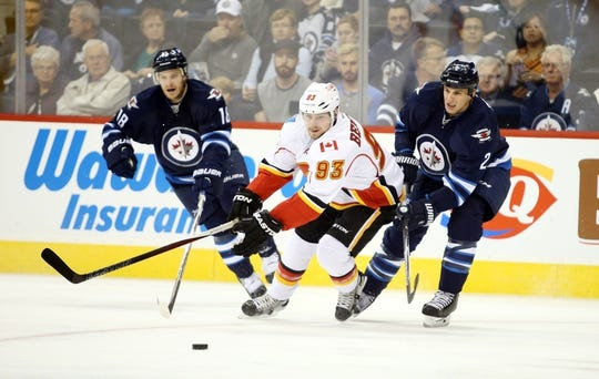 Oct 1, 2015; Winnipeg, Manitoba, CAN; Winnipeg Jets  forward  Bryan Little (18) and defenceman Adam Pardy (2) battle Calgary Flames center Sam Bennett (93) for the puck during the first period at MTS Centre. Mandatory Credit: Bruce Fedyck-USA TODAY Sports